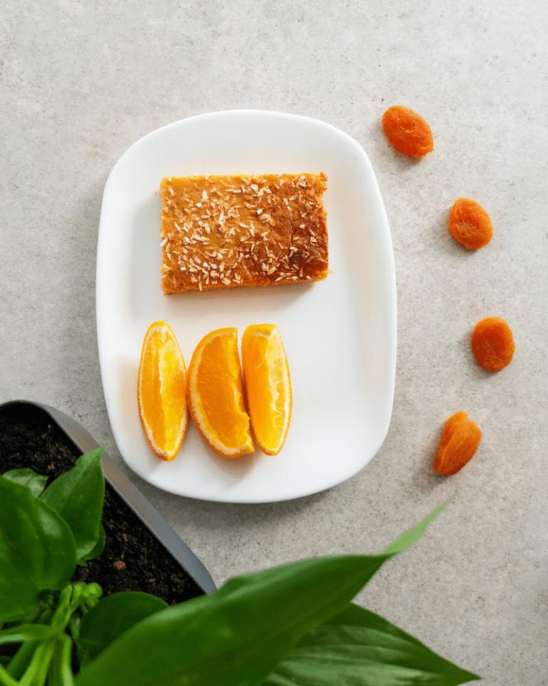 Biały talerz z kawałkiem ciasta i owocami (pomarańcze i suszone morele). Z lewej strony wystające liście rośliny. Tło stanowi szary blat.